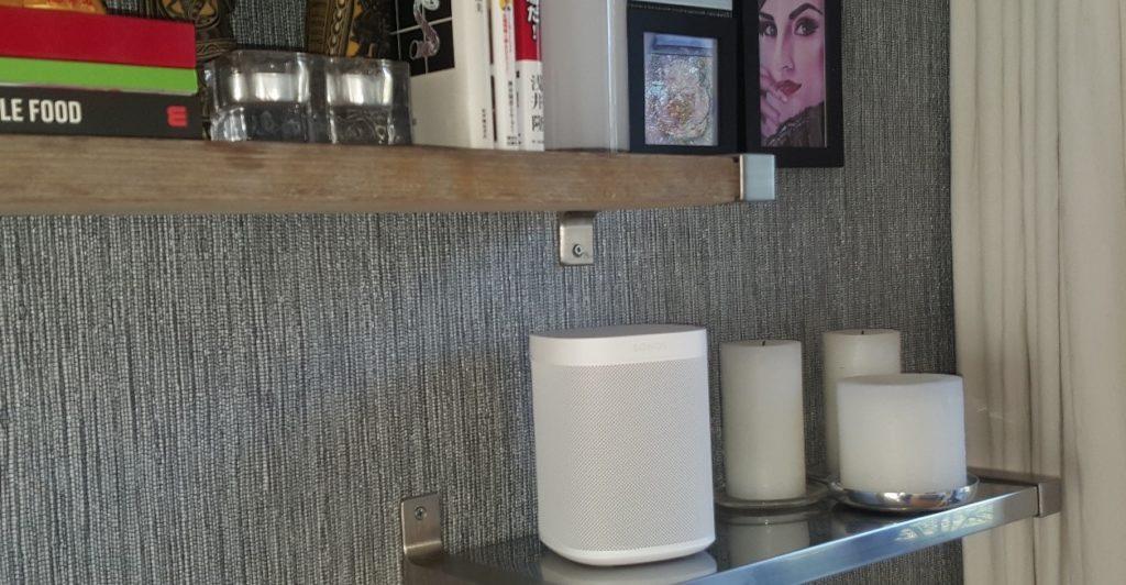 een deel van een huiskamer met de slimme speaker Sonos One op een boekenplank